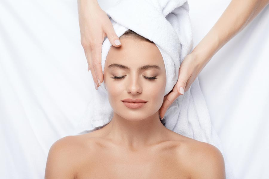 Woman lying at and getting a facial massage