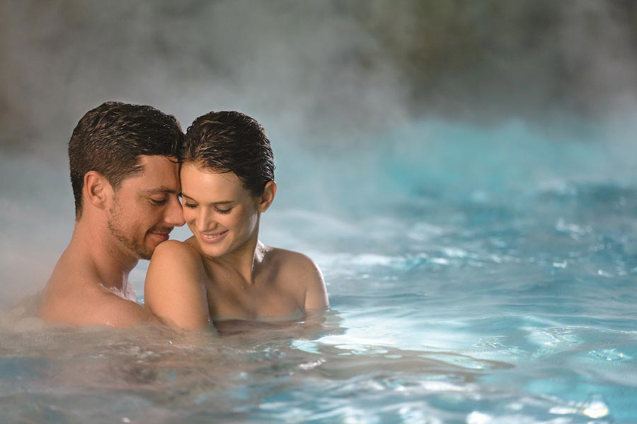 A couple is in the pool and hugging smiling in the steaming water